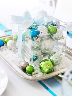 Cheery Christmas Centerpiece     For a quick centerpiece, arrange ornaments in a square vase. Tie a bow around the vase and display on a silver tray, blanketed with artificial snow and a few extra ornaments. Coordinate the color of the ornaments with your table and holiday decor.