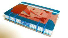 Caderno Médio David Bowie Aladdin Sane - Série Heroes  Caderno de tamanho médio, leve e resistente. Pode ser usado tanto como caderno de anotações quanto álbum de colagens, diário, livro de receitas, entre outras possibilidades.  Capa dura revestida com ilustração Stanley Chow Costura artística com linha de linho encerada Miolo em papel reciclato de alta qualidade 120g/ 240 páginas Fechamento em elástico colocado à mão Sem pauta Papel cortado e refilado à mão  O envio da peça será realizado…