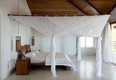 A suíte desta casa em Trancoso, litoral sul da Bahia, ocupa todo o pavimento superior, na ala íntima. Em torno da cama e dos criados, tecido mosquiteiro na cor branca, mesma cor da cortina e dos lençóis