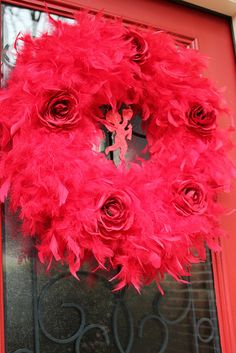 "Valentine Feather Boa Wreath  18"" wreath form wrapped with three feather boas plus artificial roses and a glittery cupid centerpiece."