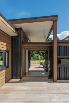 Breezeway through from the morning deck. Cedar cladding contrasting against Black Vertical Metal Cladding. Black aluminium joinery with Colorsteel longrun roofing. Auckland Waikato Coromandel