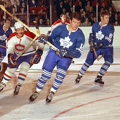 A YOUNG JIM McKENNY (ABOVE IN FOREGROUND) TURNS UP ICE AGAINST THE MONTREAL CANADIENS IN 1969-70 GAME AT MAPLE LEAF GARDENS. TEAMMATES JIM DOREY (8) AND BOB PULFORD (BACKGROUND) ALSO BEGIN HEADING THE OPPOSITE WAY. MONTREAL PLAYERS ARE YVAN COURNOYER (IN ONE-BAR HELMET) AND BOBBY ROUSSEAU (AT REAR).