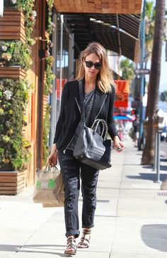 Jessica Alba loves her black boyfriend jeans by Current/Elliott, and wears them with a graphic gray t-shirt, knit moto jacket, and gladiator sandals