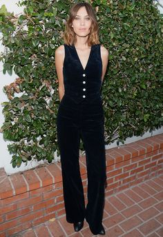 Alexa Chung in black velvety corduroy vest with high-waist trousers and boots.