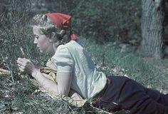 1941. Blond kvinna med röd toppluva ligger i gräset.