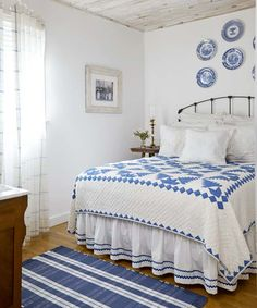 The bleached beadboard ceiling, iron bed, and blue-and-white color scheme of this bedroom fit the cottage style of this seaside home. | Photo: Laura Moss