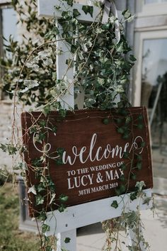 Wooden Wedding Sign Surrounded by Foliage for Barn Wedding | By Kate Gray | Classic Wedding | Rustic Wedding | Barn Wedding | White Wedding Flowers | Drip Wedding Cake | Pink Bridesmaid Dresses | Blush Bridesmaid Dresses | Wooden Wedding Signs | Wedding Decor Shed Wedding, Barn Wedding Venue, Wedding Signage, Wedding Rustic, Wedding Cake, White Wedding Flowers, Wedding White, Charlie Brear Wedding Dress, Caswell House Wedding