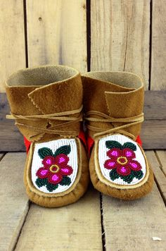 Pink Flowers with Green Leaves on White Beaded Background on Hand Tanned Moose Hide Wrap Arounds with Red Stroud Fringe. Native Beading Patterns, Beadwork Designs, Native Beadwork, Powwow Beadwork, Beaded Moccasins, Baby Moccasins, Leather Moccasins, Baby Moccasin Pattern, Native American Moccasins