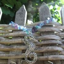 """This necklace has an intricate sea horse pendant on a necklace of bright blue and purple glass and stone chip beads. It is the perfect coloring for summer days! It is approx. 19"""" long before the pendant."""