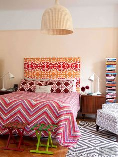 Keep proportion and room size in mind when choosing a headboard. A room with tall ceilings can handle a tall headboard, and a tall headboard -- such as this yellow-and-red block-print upholstered headboard -- can add scale to a small double bed. However, a too-tall headboard can dwarf the rest of the room./