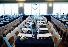 Rent blue pintuck tablecloths and white folding chairs for nautical theme wedding reception