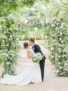 Bride and groom kissing photo under wildflower floral arch | #brideandgroom #weddingphotography #floralarch #floralarbor #gardenwedding #romanticwedding