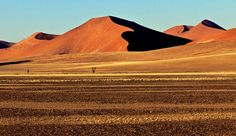 SOSSUSVLEI DUNES, NAMIBIA - Driven like waves by the wind, the golden-orange Sossusvlei Dunes—part of the vast Namib Desert—are among the world's highest, with some dunes topping 1,000 feet. They are at their most magnificent at sunrise and sunset, when the colors and shadows shift like a living painting.
