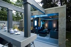 """This deck is all about comfort, with outdoor couches, slick privacy panels with colour-configurable LED lighting, real stone accents and overhead pergolas.  From """"Decked Out"""" project """"The Long Lounge Deck"""".  Deck Design by Paul Lafrance Design."""
