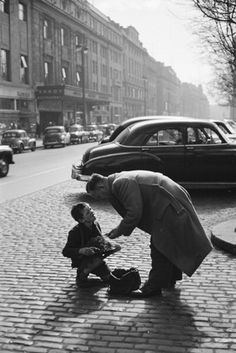 Bert Hardy A man buying heather from a boy in Upper O'Connell Street, Dublin, Eire. In the background is the Savoy restaurant. 1955