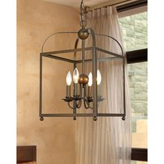 This clear glass lantern chandelier features four lights protected by a clear glass shade that allows for maximum illumination. Surrounding the lights is a metal cage with an antiqued bronze finish fo