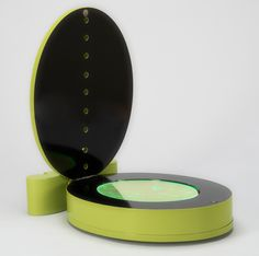 LUCIO FONTANA, Portrait d'Antonin Artaud. Multiple. Green lacquered wooden box, signed and numbered 27/80, containing 1 copper, 1 steel and 2 perspex oval discs, and book by Otto Hahn. Height 36,5 cm.