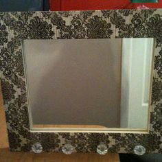 Just finished it! Made out of an unfinished frame, scrapbook paper, craft glue, & small drawer knobs. Then had a mirror cut to size.