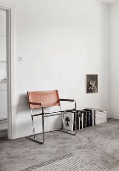 leather chair grey flooring white walls books magazines lined up on the floor
