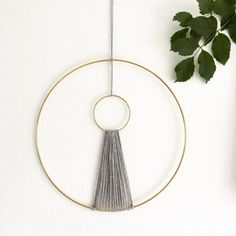 This beautiful Modern Macrame Wall Hanging is lovingly handmade in our Brighton Studio. Two Gold rings, joined together by chunky grey wool. A minimalist wall hanging with a bohemian twist. ........................................  Measurements:  Width of large ring: 12 inches  Width of small ring: 3 inches  ..........................................  This item will be dispatched within 20 working days of ordering - sorry for the inconvenience but we are currently waiting for a delivery…