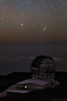 Andromeda and Triangulum Galaxy, each of the two home to many billions of stars, seen above the Roque de los Muchachos Observatory on the top of La Palma image by Babak Tafreshi