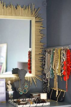 DIY mirror. Paint mirror  wooden dowels gold. Cut dowels into various lengths  attach to the back of the mirror.