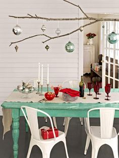 Festive Centerpiece  Branch out from conventional tablescapes by using an extra-long tree limb as a platform for displaying ornaments. Simply knot lengths of twine around the branch and hang it from a row of five or six ceiling hooks.