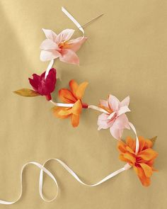 Use continuous-petal flowers made without a stamen (roll the strip tightly around itself, and secure with floral tape). Thread an upholstery needle with double-sided satin ribbon; run needle up through centers of flowers. Leave four inches between flowers.