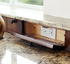 I love this idea! I'm storing this idea away for when I eventually redo my kitchen. Hide all those needed kitchen outlets, and create a new level of counter top at the same time. Store cords inside when not in use, to keep your counters tidy.