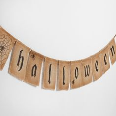 "Welcome guests to your home with our artfully distressed ""Happy Halloween"" garland, handcrafted of burlap and accented with spiders for creepy-crawly fun."