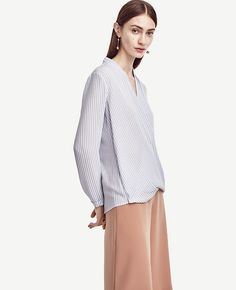 """Top line: in a silhouette-slimming wrap style, this striped essential flaunts the season's freshest hues. V-neck with crossover front and snap closure. Long sleeves with button closure. Shoulder pleats. Forward side seams. Back yoke. Back shirttail hem. 24"""" front length; 26 3/4"""" back length."""