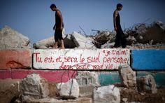 25/05 - Palestinos caminham sobre uma parede pintada com o graffiti em Francês 'eu te amo, você é e continuará a ser o único na minha vida' no porto da Cidade de Gaza