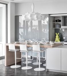 This impeccable all-white modern kitchen gets just the right dose of embellishment, courtesy of the FLOS Zeppelin Pendant light.