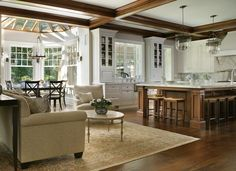 Love the mix of white and stained wood.  Lovely large island and room for a round table.