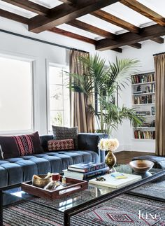 Vintage textiles on the living room's sofa pillows and the square leather ottoman from Mosaik temper the wood floors that were darkened to a deep walnut-toned finish. The wood floors' hue echoes the post-and-beam ceiling— originally a blond shade.