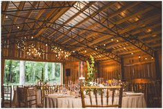 A collection of twinkling grape vine balls and elegant Clair chandeliers bring unique and glittering style to a rustic setting at Rock Quarry Farm.  Flowers: Eclectic Sage, Planner: A Swanky Affair, Photo: Michael Moss Photography.