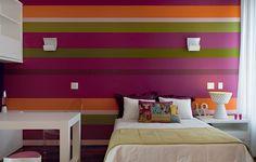 O colorido tem a cara da adolescente que habita o quarto. A parede tem uma paleta de cores energéticas. A arquiteta Andrea Murao elegeu os tons de roxo, verde e laranja e criou listras que se repetem, ora finas, ora grossas
