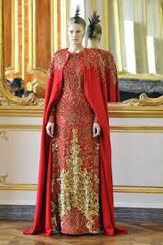 McQueen again shows the overall silhouette of the tighter fitting gowns and the cape-like outer garments worn by women in the late middle ages.