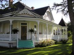 what a beautiful old country home....  awesome wrap around porch, and i love the teal steps