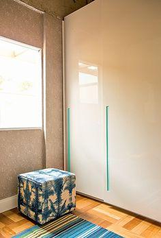 Com puxadores em cava na cor turquesa, os armários brancos do projeto da arquiteta Letícia Arcangeli permitem as estampas marcantes do pufe e do tapete. Piso de cumaru e papel de parede completam o closet