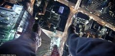 Dangerous: James Charlick, feet dangling in a vertigo inducing shot from the top of a central London crane, says that he never puts his life in danger when taking his pictures.