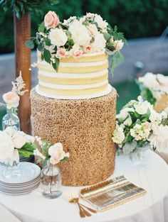 Gold and white #wedding cake topped by blush florals. Image by Erich McVey. See more in the Spring 2014 issue of Weddings Unveiled.