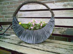 bloembak van ijzeren frame met fietsband, gaas, mos en salim