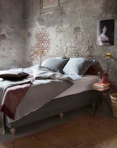 Bedroom with unfinished wall & exposed brick