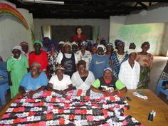 Group picture of the widows at the Widow Care Center in Kenya with the yo-yo quilt they made together as a project.