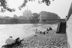 1990, Paris, France --- Couples and others relax on an embankment of the Seine on Ile St.-Louis on a sunny day. Notre Dame cathedral can be seen across the water, on the Ile de la Cite. --- Image by © Owen Franken/CORBIS - Photograph by Owen Franken  http://owenfranken.photoshelter.com/image/I0000VMCtDQH0BZ4#