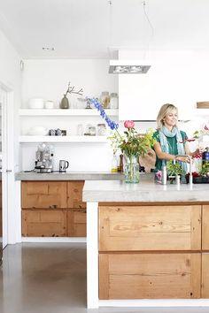 Cucina in muratura stile moderno, semplice e lineare - top e pavimenti in cemento, sportelli in legno chiaro, pareti bianche - isola centrale
