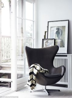 An Arne Jacobsen Egg chair and monochrome throw complement an understated painting by Swedish artist Harry Booström in the study