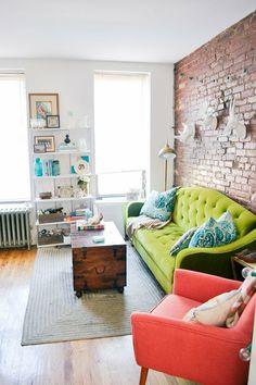weißes Regal, grünes Sofa, roter Sessel, grauer Teppich, Kisten als Tisch, Wohnzimmer gestalten