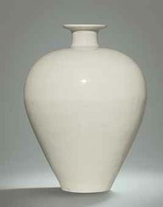 A VERY RARE DING MEIPING NORTHERN SONG DYNASTY Elegantly-proportioned, the vase is finely potted with an ovoid body tapering from a high shoulder to a narrow base, surmounted by a short and gently waisted neck flaring to an everted mouth with finger-grooved rim. It is covered overall with a smooth ivory-tinted clear glaze. 9 3/4 in high